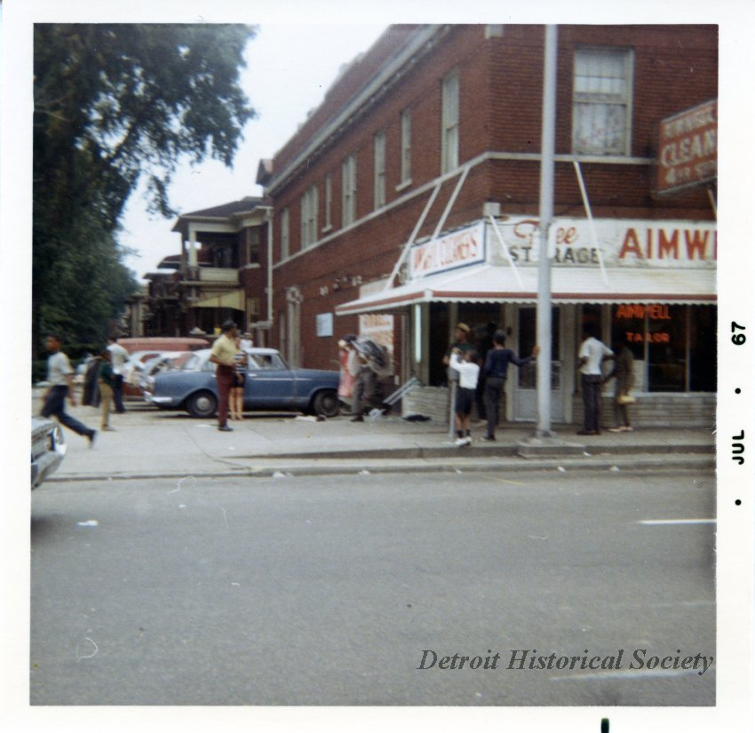 Color photo depicting Aimwell Cleaners at 12 St. and Atkinson Avenue during the 1967 Civil Disturbance, 1967 – 2018.076.031